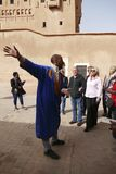 Mohammed the guide leads his tour group. OUARZAZATE, MOROCCO - FEB 17, 2019 - Mohammed the guide leads his tour group in the Kasbah Taourirt, Ouarzazate stock photo