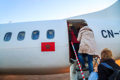 Ouarzazate, Morocco - Feb 28, 2016: passengers boarding airplane of Royal Air Morocco. People climbing ramp on background, rear vi Royalty Free Stock Photos