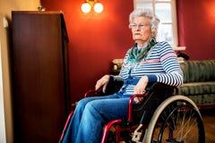 Oublié par la famille, femme supérieure triste au fauteuil roulant Photos stock