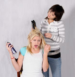 Ouch. Pretty blonde and brunette cosmetology students working on hair royalty free stock images
