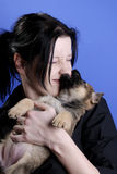 Ouch. Portrait of a woman and her german shepherd puppy on blue background stock image