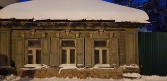 Oud één-verhaal blokhuis op de straat in de winter stock fotografie