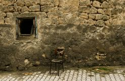 Oud adandoned stoel voor de oude onderbrekingsmuur in de straat royalty-vrije stock afbeeldingen