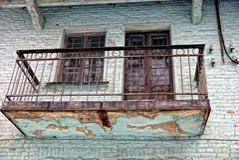 Oud balkon op de groene bakstenen muur van het gebouw Stock Afbeeldingen