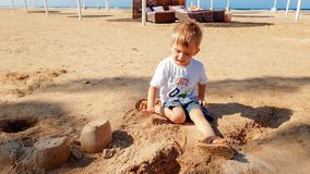 Oud beeld van 3 jaar weinig zitting van de peuterjongen op het overzeese strand en de bouw kasteel van nat zand royalty-vrije stock foto's