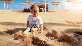 Oud beeld van 3 jaar weinig zitting van de peuterjongen op het overzeese strand en de bouw kasteel van nat zand royalty-vrije stock afbeeldingen