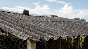 Oud Beschimmeld Golfdak van Verlaten Aziatische Kippenkippenren met Rusty Wire Fence - Blauwe Heldere Hemel met Wolken - Natuurli royalty-vrije stock foto