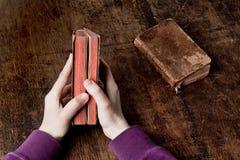 Oud boek in handen Stock Foto