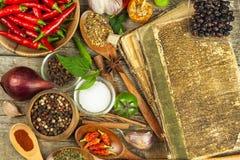 Oud boek van het kokenrecepten Culinair boek als achtergrond en recepten met diverse kruiden op houten lijst Stock Afbeeldingen