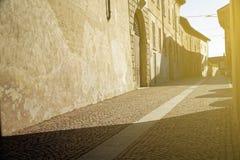 Oud cobbled straat in Italië, met schaduwen en zonnestraal royalty-vrije stock foto's