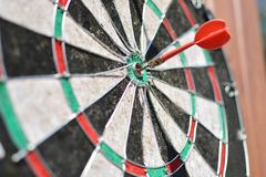 Oud dartboard met pijl die een doel raken stock fotografie