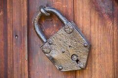 Oud deurslot Oud gesloten hangslot met ringen op oude houten raadsdeur stock foto