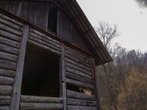 Oud die logboekhuis in de bergen wordt verlaten stock foto