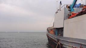 Oud die vissersvaartuigboot of schip dichtbij de zeehaven wordt vastgelegd stock video