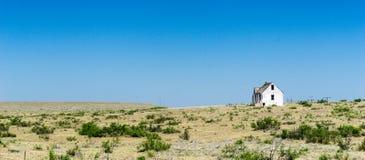 Oud dilapidated en verlaten wit blokhuis op de verre prairie in middlew van nergens onder een blauwe hemel royalty-vrije stock afbeeldingen