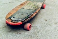 Oud doorstaan skateboard op concrete oppervlakte Stock Afbeeldingen
