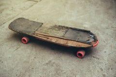 Oud doorstaan skateboard op concrete oppervlakte Royalty-vrije Stock Afbeeldingen