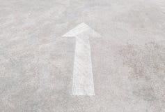 Oud en bleek wit geschilderd de pijlteken van de close-upoppervlakte op de vloer geweven achtergrond van de cementstraat Royalty-vrije Stock Afbeelding