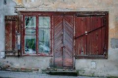 Oud en ruw booden deur en windods in de oude stad van Vilnius Stock Afbeelding