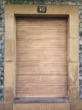 Oud en wijnoogst gesloten venster met houten blind in een muur van de granietsteen en blauwe tegels, met nummer 40 op bovenkant royalty-vrije stock afbeelding