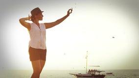 Oud-filmeffect lengte: een vrouw bevindt zich op de strandboulevard en neemt een beeld van zich stock video