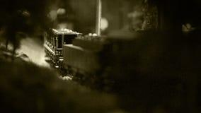 Oud filmeffect: model van een oude trein met de locomotief die zich langs het spoor bewegen stock videobeelden
