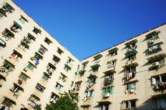 Oud flatgebouw met rijen van vensters onder blauwe hemel Royalty-vrije Stock Afbeeldingen