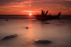 Oud gebroken bootwrak op de kust, een bevroren overzees en een mooie blauwe zonsondergangachtergrond Royalty-vrije Stock Afbeeldingen