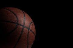 Oud gebruikt basketbal op zwarte achtergrond Stock Fotografie