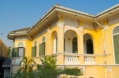 Oud geel huis - buiten eerste verdiepingmening royalty-vrije stock afbeelding