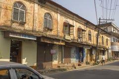 Oud geel sjofel twee-verhaal huis op een Indische straat met mensen en autoverkeer stock foto