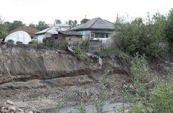 Oud geruïneerd blokhuis op de rand van een klip die gevaarlijk land op de rivierbank afbrokkelt in een Siberisch dorp royalty-vrije stock afbeelding