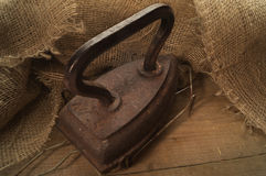Oud gietijzer op een jute, op oude houten lijst Royalty-vrije Stock Fotografie