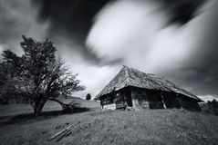 Oud griezelig verlaten landbouwbedrijfhuis in zwart-witte kleur Een oud, lang-verlaten huis, tegen de geschotene achtergrond van  Stock Afbeeldingen