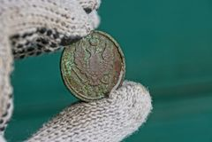 Oud groen Russisch muntstuk met een adelaar in de vingers stock foto