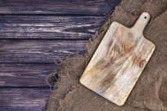 Oud hakbord op donkere houten achtergrond, scherp dienblad over jutetafelkleed, hoogste mening royalty-vrije stock foto's