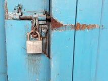 Oud hangslot en blauwe deur Stock Foto