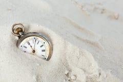 Oud horloge in het zand stock fotografie