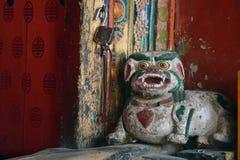 Oud houten cijfer van een traditionele Tibetaanse sneeuwleeuw bij de deur in het Hemis-Klooster, Himalayagebergte, India Stock Fotografie