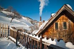 Oud houten die plattelandshuisje met heuvel door sneeuw op achtergrond wordt behandeld Heldere koude de winterdag in het bergenla Royalty-vrije Stock Foto