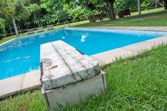 Oud houten duikplank en zwembad met transparant water stock fotografie