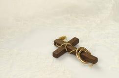 Oud houten kruis met gouden ringen op wit kant Stock Afbeelding