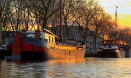Oud houten schip twee in zonsonderganglicht in het rivierkanaal door sh stock afbeeldingen