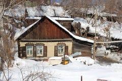 Oud houten Siberisch die huis in het dorp van dilapidated in de sneeuw met sneeuwbanken wordt behandeld royalty-vrije stock afbeelding