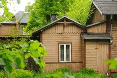 Oud houten, traditioneel huis onder de bomen Stock Foto's