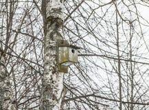 Oud houten vogelhuis op een boom Op de achtergrond van takken royalty-vrije stock afbeeldingen
