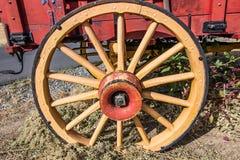 Oud Houten Wagenwiel op Rode Wagen royalty-vrije stock afbeeldingen