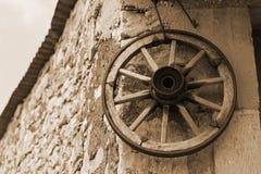 Oud houten wiel op een muur van royalty-vrije stock afbeelding