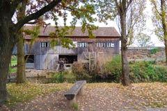 Oud houtplattelandshuisje met grote boom in de kant van het land jpg Stock Foto's