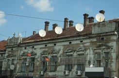 Oud huis bezet door satellietantennes Stock Afbeeldingen
